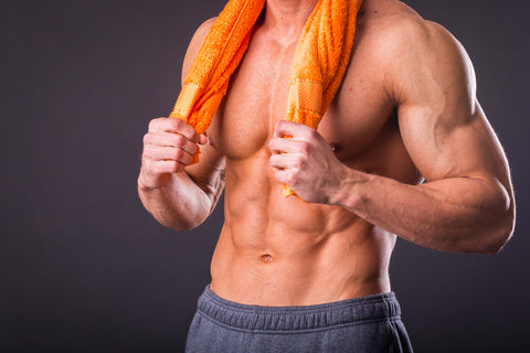 a lean and muscular man with a gym towel around his neck