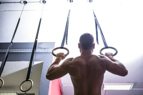 Back view of muscular man doing ring gymnastics in crossfit gym