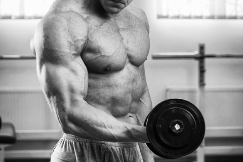 Muscular guy working with free weights