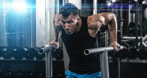 Young muscular man during workout in the gym
