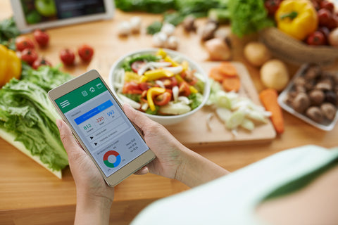 Woman using calorie counter application on her smartphone