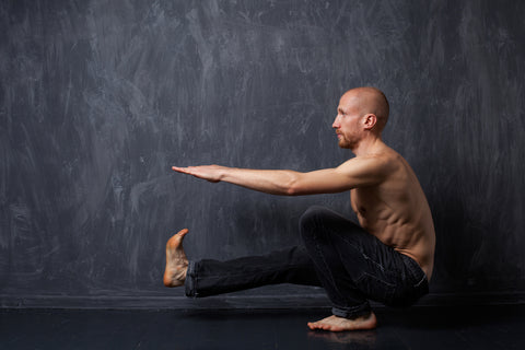 A man with a naked torso doing pistol squats