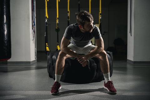A man resting post-workout in a gym.