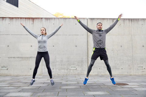 A man and a woman doing jumping jacks.