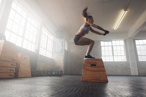 A girl doing box jumps in a gym.