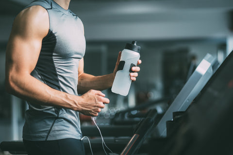 young man in sportswear running on treadmill at gym and holding bottle of water