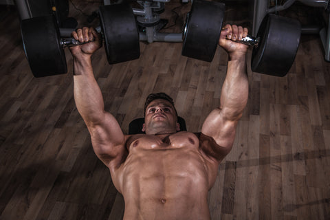 A man doing the dumbbell bench press.