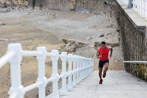 Black fit runner sprinting on a ramp at the beach