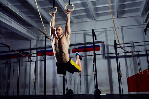 Muscle-up exercise young man doing intense cross fit workout at the gym
