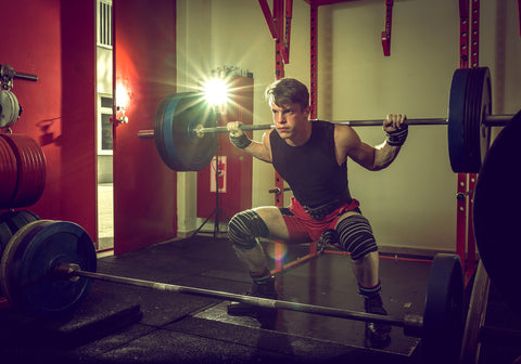 Young teenage man doing squats in indoor gym club.