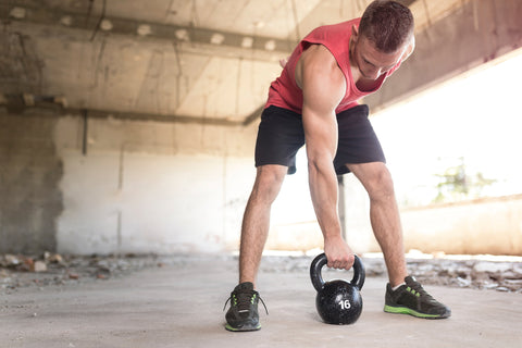 Young, muscular, athletic built man working out, lifting a kettlebell weight in an abandoned ruined building
