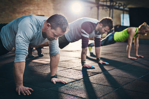Three men doing plank jacks in a gym.