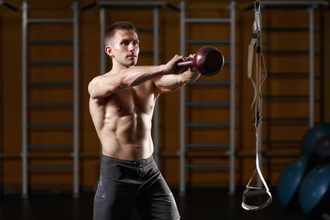 Young athlete doing kettlebell swings