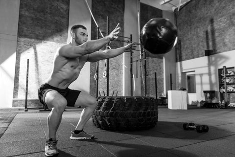Handsome concentrated man looking at the medicine ball