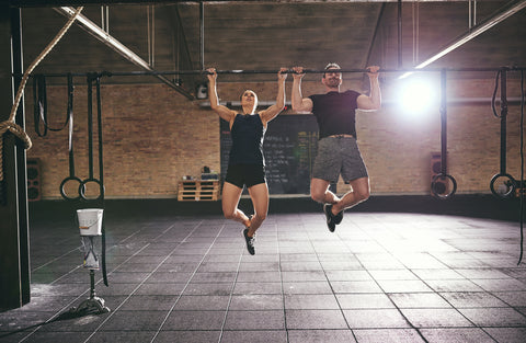 A man and woman doing pull-ups in the gym.