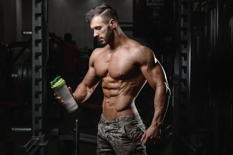 Handsome athletic fitness man holding a shaker and posing gym