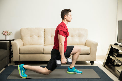A man doing dumbbell lunges at home.