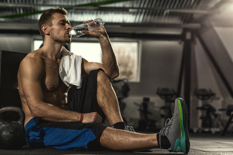 A strong man drinking water in a gym post-workout.