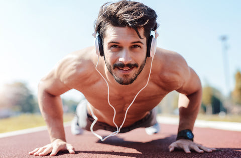 Young sportsman doing push ups and listening to music with headphones.