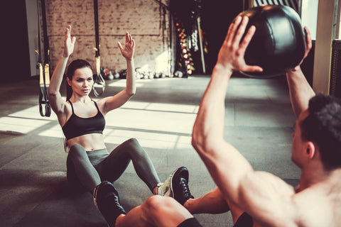 Beautiful young sports couple is working out with medicine ball in gym