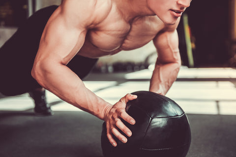 Handsome young muscular sportsman is working out with a medicine ball in gym