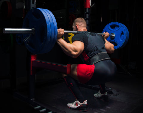 Professional athlete does squats with a bar in the gym