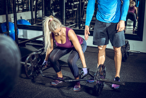 Attractive blonde woman doing trap bar deadlift exercise with help of her personal trainer.