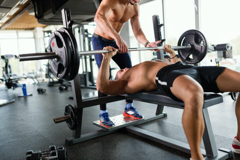 A man doing a bench press in a gym.