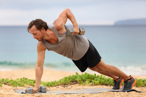 Fit man doing renegade rows on a beach