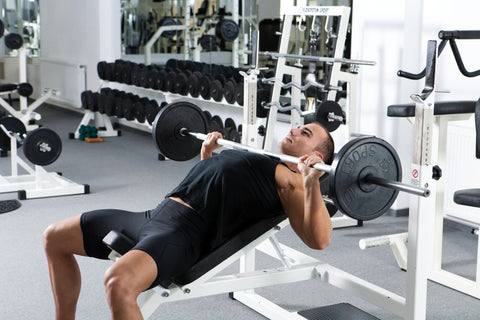 A man doing an incline bench press in a gym.