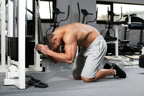 young bodybuilder training in the gym: Abdominals - Cable Crunch, finish position