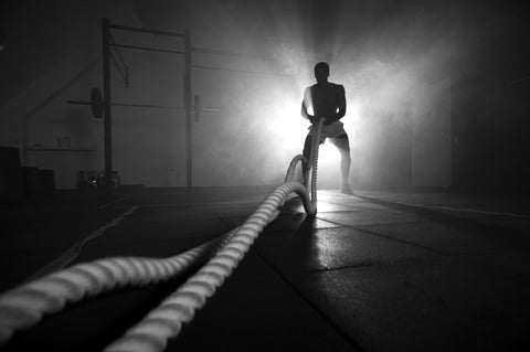 Silhouette of man working out with battle ropes at gym