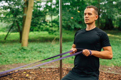 A man working out with a resistance band in a park.