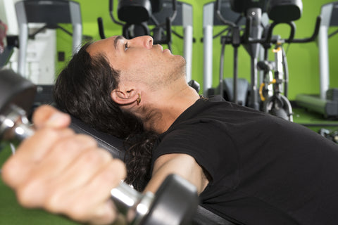 A man doing incline dumbbell flyes in a gym.