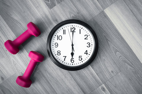 Clock and weights on wooden background.