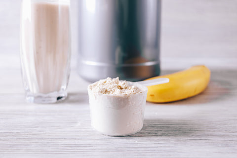 Scoop with protein powder, banana and glass on the table close-up