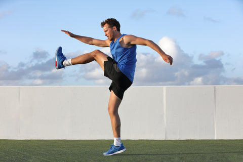 Runner man getting ready to run doing warm-up dynamic leg stretch exercises
