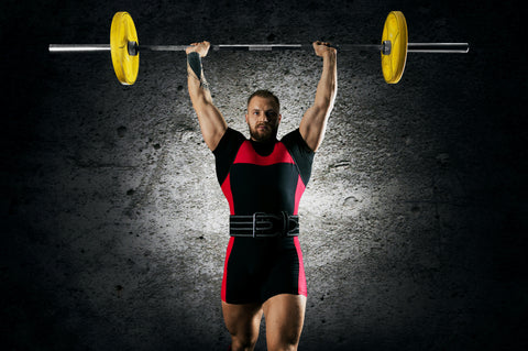 The athlete is standing with a barbell above his head