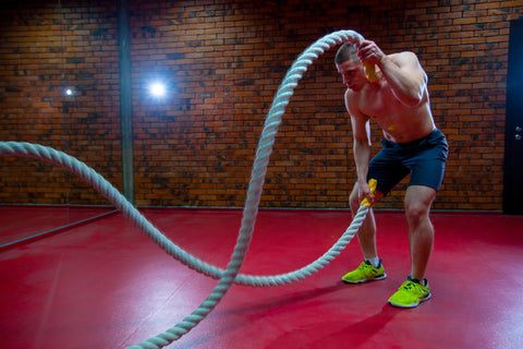 Muscular Shirtless Man in a Gym Exercises with Battle Ropes