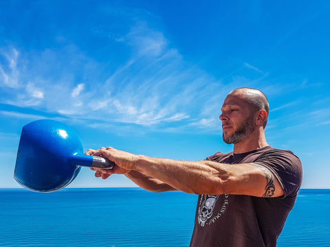 A man working out with a blue kettlebell.