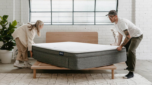 Man and woman putting mattress on bed base