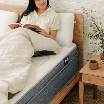Woman sitting up on bed reading magazine on Eva Bedroom products