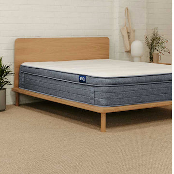 Couple placing matress on to timber bed frame