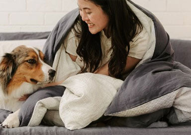 Girl and dog wrapped in grety hemp linen sheets