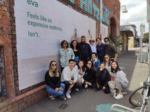 Eva Team in front of Eva Mattress street poster