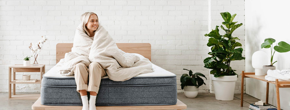 Girl smiling wrapped in oat coloured hemp linen duvet sitting on the Eva Mattress and Timber Bed base