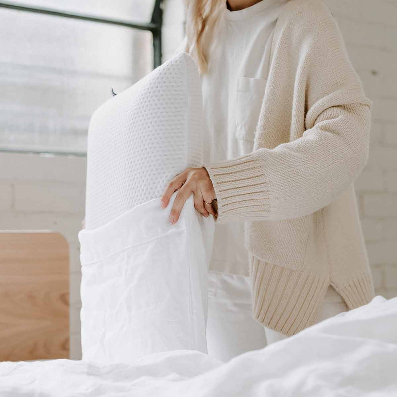 Woman putting Eva Pillow in a White Hemp Linen Pillowcase