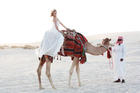 the Johanna wedding dress lifestyle side on with bride riding a camel