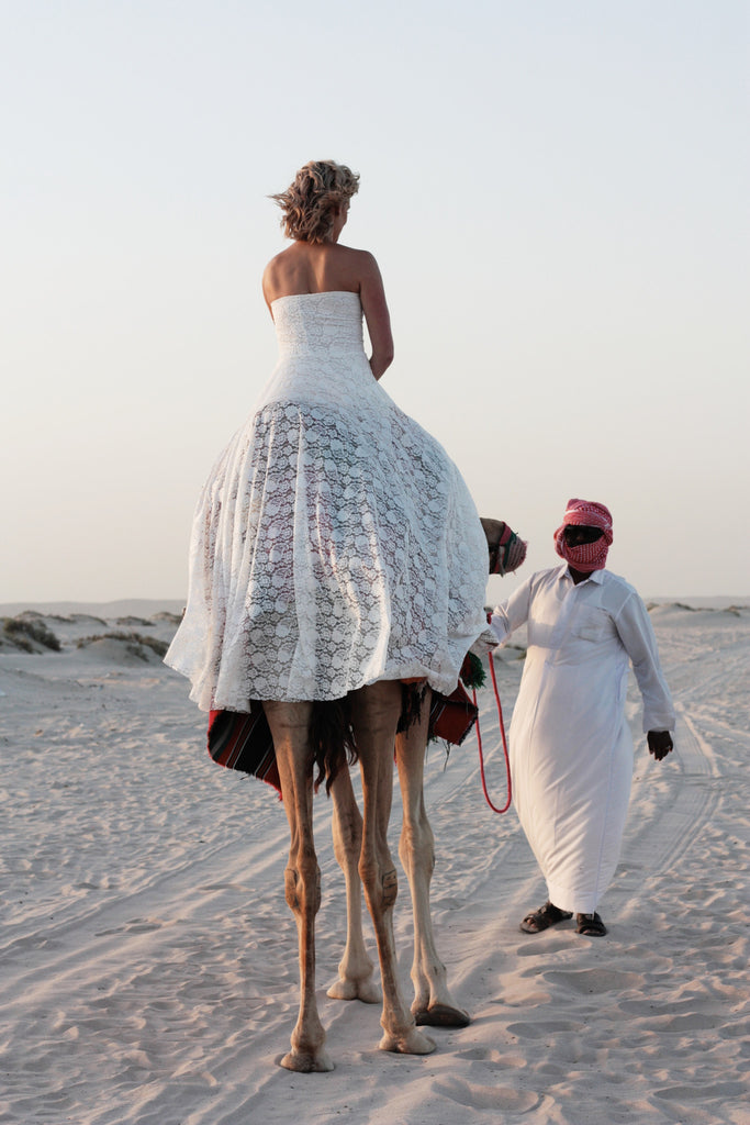The Johanna Wedding Dress lifestyle shot from behind with bride riding a camel