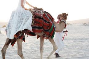 The Johanna Wedding Dress cropped side on with bride riding a camel